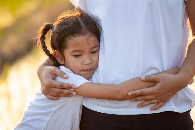 Ragazza asiatica triste del bambino che abbraccia sua madre nella risaia con la luce solare
