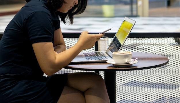 Ragazza asiatica utilizzare il telefono cellulare e notebook sul tavolo del caffè