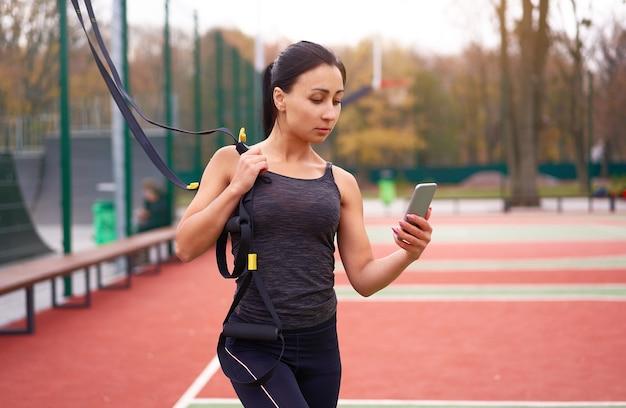 Ragazza atleta formazione utilizzando trx su sportground