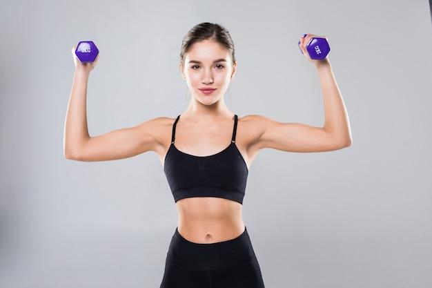 Ragazza atletica di forma fisica con le teste di legno su una parete bianca