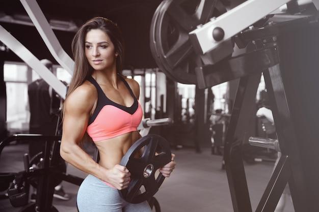 Ragazza atletica sexy di forma fisica che risolve in palestra