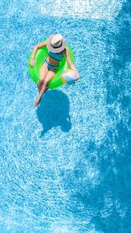 Ragazza attiva nella vista aerea aerea della piscina dall'alto, il bambino si rilassa e nuota sulla ciambella ad anello gonfiabile e si diverte in acqua in vacanza con la famiglia, località di villeggiatura tropicale