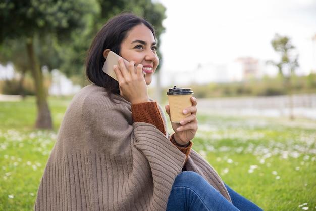 Ragazza attraente allegra che ha conversazione piacevole del telefono