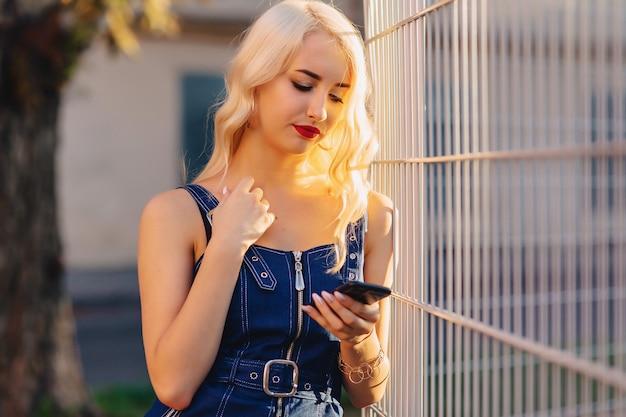 Ragazza attraente bionda emotiva in occhiali da sole con il telefono nel sole estivo urbano