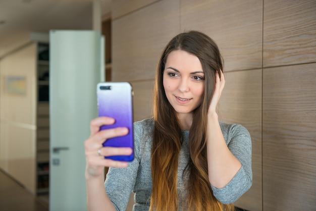 Ragazza attraente che fa selfie sul fondo di legno della parete a casa. social network, selfie, tema dell'autoritratto.
