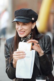 Ragazza attraente che mangia panino per strada