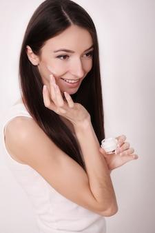 Ragazza attraente che mette la crema anti-invecchiamento sul viso