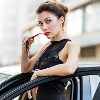 Ragazza attraente che sta vicino all'automobile