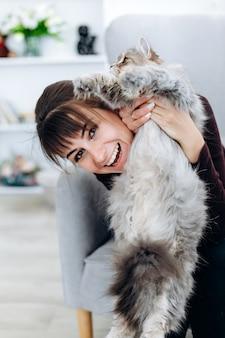 Ragazza attraente che tiene un bellissimo gatto nelle sue mani