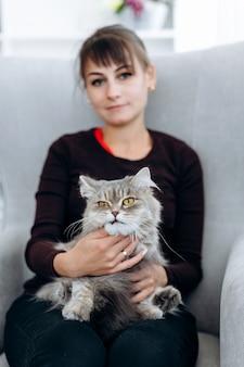 Ragazza attraente che tiene un gatto sul suo giro, vista alta vicina