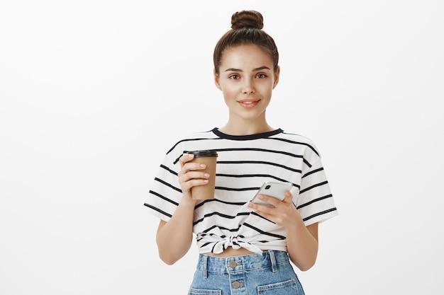 Ragazza attraente che utilizza smartphone mentre beve il caffè, che tiene tazza e telefono cellulare