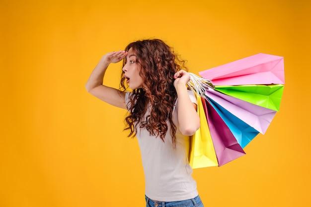 Ragazza attraente con capelli ricci e sacchetti della spesa variopinti che cercano le vendite isolate sopra giallo
