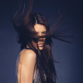 Ragazza attraente con i capelli di volo che posano nello studio