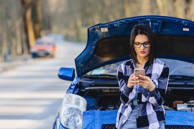 Ragazza attraente con il telefono vicino al cofano aperto dell'automobile