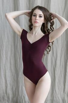 Ragazza attraente del brunette che propone in un vestito di bodie su una priorità bassa grigia del tessuto. luce naturale dalla finestra