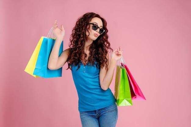 Ragazza attraente del brunette con capelli ricci isolati sopra il colore rosa con gli occhiali da sole ed i sacchetti di acquisto in sue mani. concetto di vendita e shopping