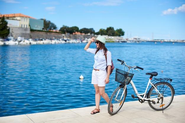 Ragazza attraente felice in occhiali da sole e con zaino in sella a una bicicletta lungo marciapiede pietroso