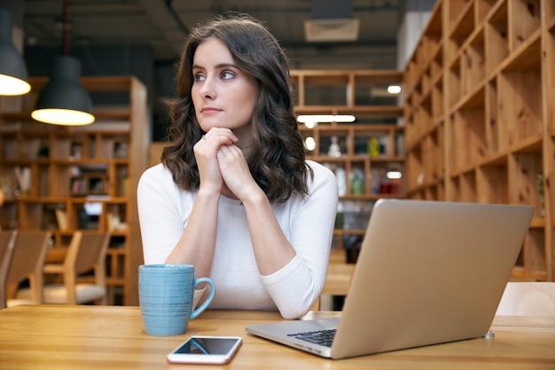 Ragazza attraente giovane donna elegante in abiti casual, seduto a un tavolo in un caffè con un computer portatile con le mani sotto il mento e guarda pensieroso al lato