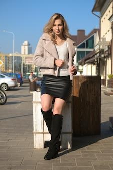 Ragazza attraente in breve cappotto di pelle di pecora, gonna di pelle e stivali di camoscio divertendosi nel soleggiato giorno di autunno