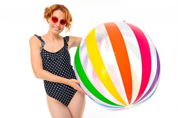Ragazza attraente in costume da bagno monopezzo nero retrò e occhiali da sole con una palla a strisce per acqua su uno sfondo bianco