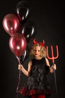 Ragazza attraente in costume dei diavoli di halloween