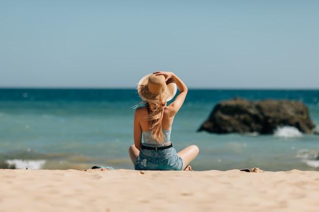 Ragazza attraente in occhiali da sole e cappello si trova sulla sabbia calda