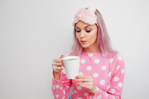 Ragazza attraente in pigiama rosa e maschera per dormire godendo il suo caffè mattutino