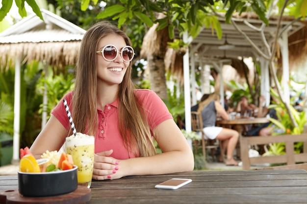 Ragazza attraente in tonalità rotonde alla moda che riposa le mani sul tavolo di legno con il telefono cellulare, frullato fresco e ciotola di frutta mentre si fa colazione al caffè all'aperto, aspettando gli amici, sorridendo e guardando