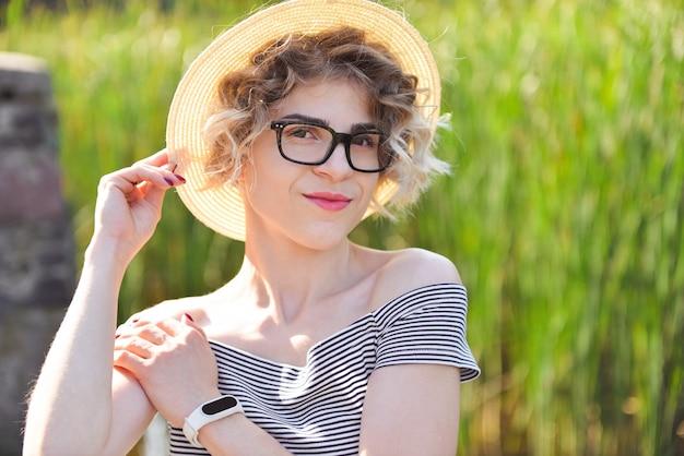Ragazza attraente in un cappello e grandi vetri con l'orlo in un vestito a strisce che sta sulla natura dentro