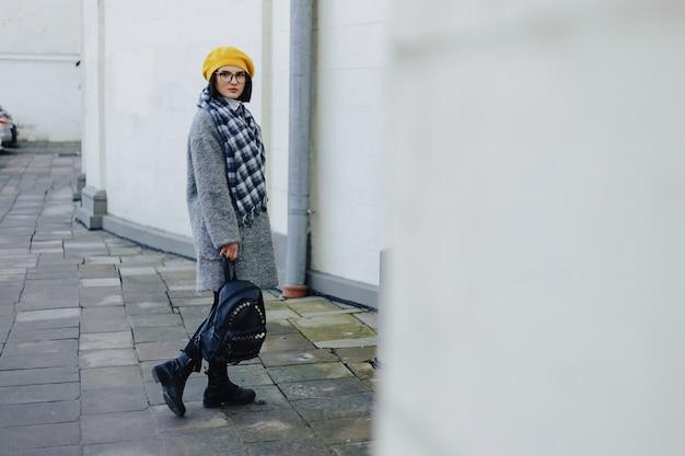 Ragazza attraente in vetri nel cappotto e nella camminata gialla di stile libero del berretto