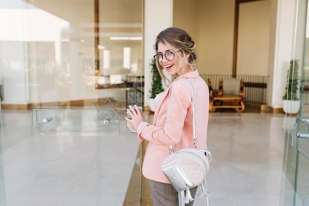 Ragazza attraente sorridente che entra nella grande porta di vetro in ufficio, hotel, centro di affari. indossare occhiali alla moda, pantaloni grigi, giacca rosa, zaino argento.