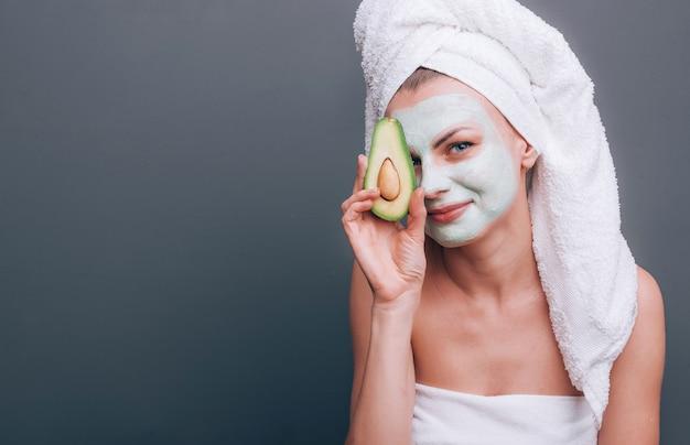 Ragazza avvolta in un asciugamano con una maschera cosmetica sul viso e avocado nelle sue mani