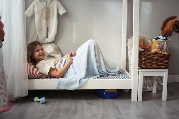 Ragazza bambino gioca nel piccolo letto con i giocattoli, in realtà