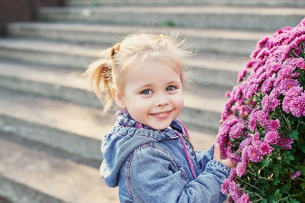 Ragazza bambino in un parco vicino a un letto di fiori di crisantemi in autunno