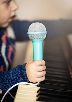 Ragazza bambino, pianoforte e microfono giocattolo.