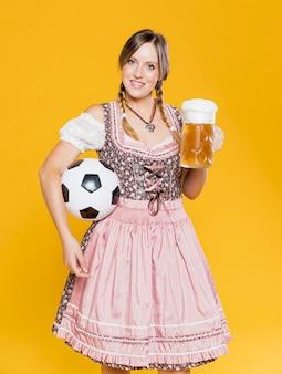 Ragazza bavarese che tiene palla e boccale di birra