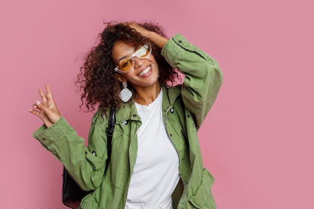 Ragazza beata con l'acconciatura africana che ride durante il tiro di foto dello studio. indossa orecchini eleganti, occhiali da sole e guarnizione verde. sfondo rosa.