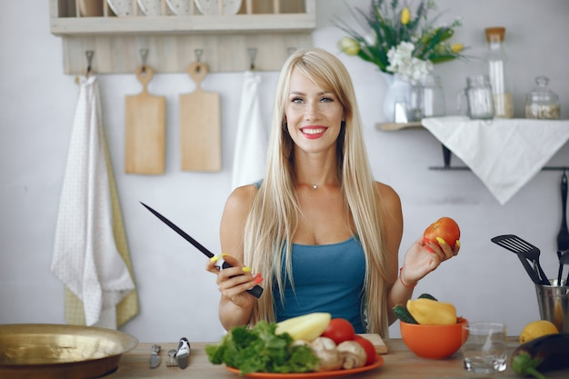 Ragazza bella e sportiva in una cucina con verdure