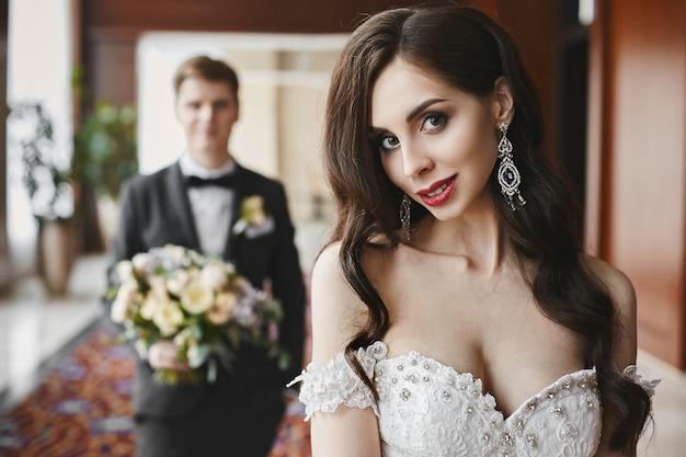 Ragazza bellissima e tettona modella bruna con trucco luminoso e corpo sexy in un abito lungo alla moda con seducente decollete e orecchini di lusso con diamanti che sorridono e posano all'interno