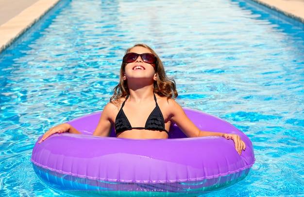 Ragazza bikini con occhiali da sole e anello piscina gonfiabile