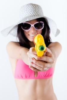 Ragazza bikini con pistola a spruzzo guardando a porte chiuse