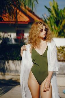 Ragazza bionda abbronzatura e relax in piscina