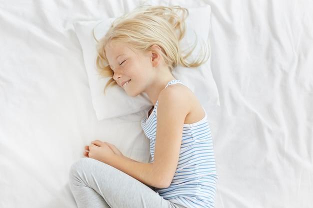 Ragazza bionda adorabile che ha sogni d'oro sul cuscino bianco, arrotolantesi nella palla. ragazza abbastanza lentigginosa con capelli lisci chiari che sorride nel sonno, godendo di un'atmosfera tranquilla nella sua confortevole camera da letto
