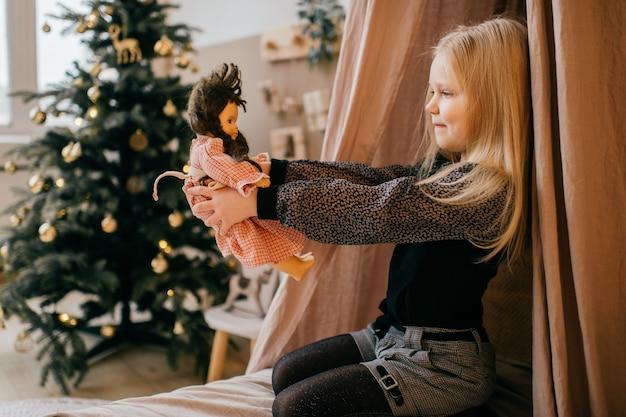 Ragazza bionda adorabile che siiting nella stanza di bambini con il wigwam e l'albero di natale e che esamina la sua bambola amorosa in sue mani