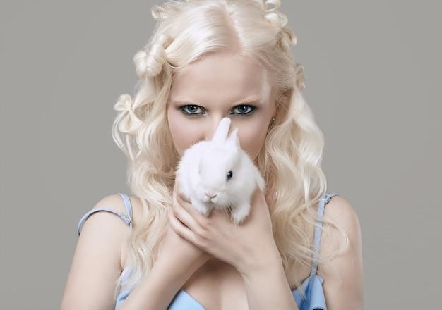 Ragazza bionda albina in abito elegante in posa con simpatico coniglietto