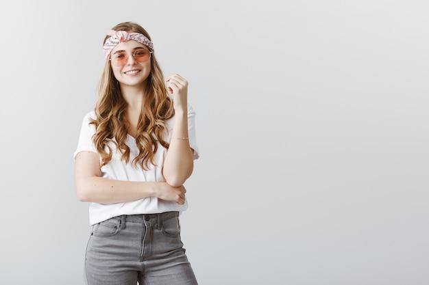 Ragazza bionda alla moda in occhiali da sole che sembrano interessati