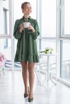 Ragazza bionda allegra di eleganza nella condizione interna con una tazza dopo la finestra di mattina