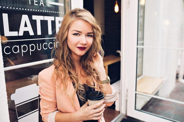 Ragazza bionda attraente del ritratto con capelli lunghi che si raffreddano sulla terrazza nella caffetteria. ha labbra vinose, tiene la tazza