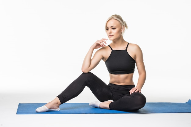 Ragazza bionda avere un momento di relax dopo l'esercizio di pratica sportiva sul pavimento seduto su una mappa dello sport