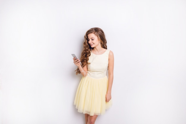 Ragazza bionda carina che ascolta la musica sugli auricolari sullo smartphone si diverte. sorride ampiamente e gioca con il suo vestito giallo. aveva lunghi capelli biondi ricci
